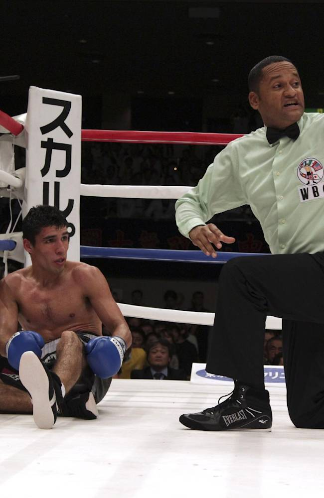 Mexican challenger Alberto Guevara sits on the mat after being knocked down by Japanese champion Shinsuke Yamanaka in the ninth round of their WBC bantamweight title bout in Tokyo, Sunday, Nov. 10, 2013. Yamanaka knocked out Guevara in the round to defend his title