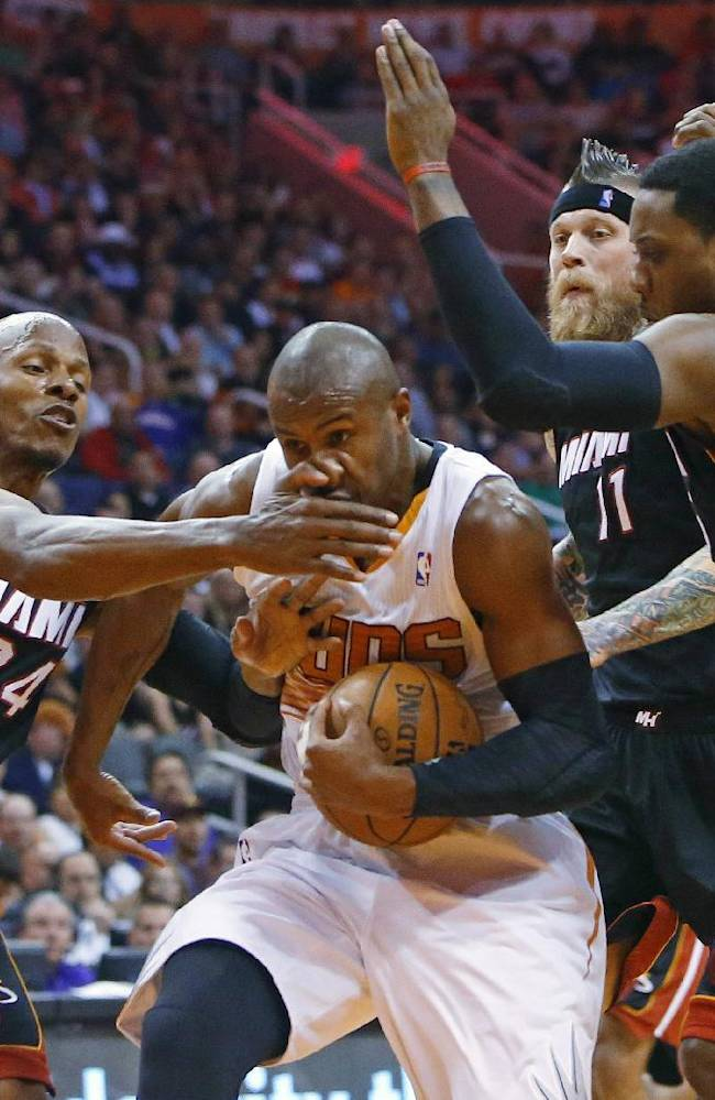 Phoenix Suns guard Leandro Barbosa (10) gets his nose bent to the side by Miami Heat guard Ray Allen (34) during the first half of an NBA basketball game Tuesday,  Feb. 11, 2014, in Phoenix