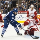 Toronto Maple Leafs' Joffrey Lupul (19) goes to the net against Detroit Red Wings goalie Jonas Gustavsson during second-period preseason NHL hockey game action in Toronto, Friday, Oct. 3, 2014 The Associated Press