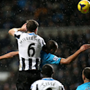 Newcastle United's Mike Williamson, left, vies for the ball with Tottenham Hotspurs' Younes Kaboul, right, during their English Premier League soccer match at St James' Park, Newcastle, England, Wednesday, Feb. 12, 2014