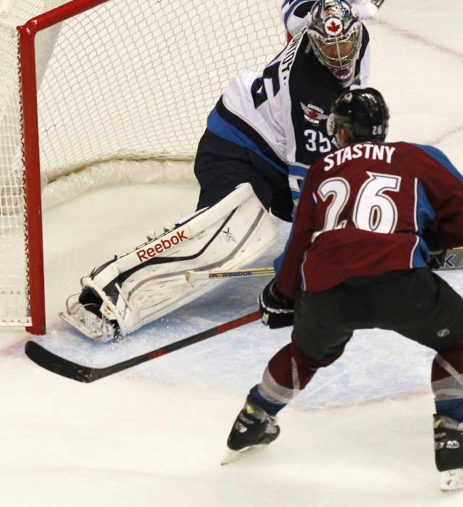 Colorado Avalanche center Paul Stastny, front, puts the puck in the net for the go-ahead goal past Winnipeg Jets goalie Al Montoya in the third period of the Avalanche's 3-2 victory in an NHL hockey game in Denver on Sunday, Oct. 27, 2013
