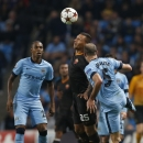 Manchester City's Pablo Zabaleta, right, and his teammate Fernandinho, left, fight for the ball with Roma's Jose Holebas during their Champions League group E soccer match between Manchester City and Roma at the Etihad Stadium, Manchester, England, Tuesda