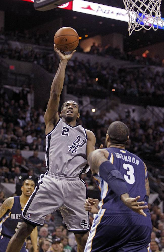 In this April 6, 2014 file photo, San Antonio Spurs' Kawhi Leonard (2) puts up at shot against Memphis Grizzlies'  James Johnson (3) during the second half of an NBA basketball game, in San Antonio. He has been called the future face of this franschise, and when Tim Duncan, Manu Ginobili and Tony Parker are done ruling the roost, he's ready to take over