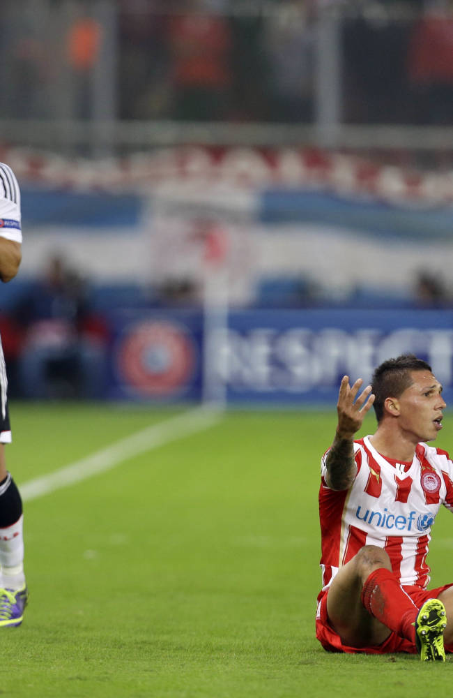 Olympiakos' Jose Holebas, right, and Benfica's Enzo Perez both make complaints to the referee during their Champions League group C soccer match at the Karaiskaki stadium, in the port of Piraeus, near Athens, Tuesday, Nov. 5, 2013
