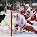 Pittsburgh Penguins' Nick Spaling (13) watches the puck land on the back of the net as Detroit Red Wings goalie Jimmy Howard (35) dives across the goal crease with center Cory Emmerton (25) behind him during the second period of a NHL pre-season hockey g