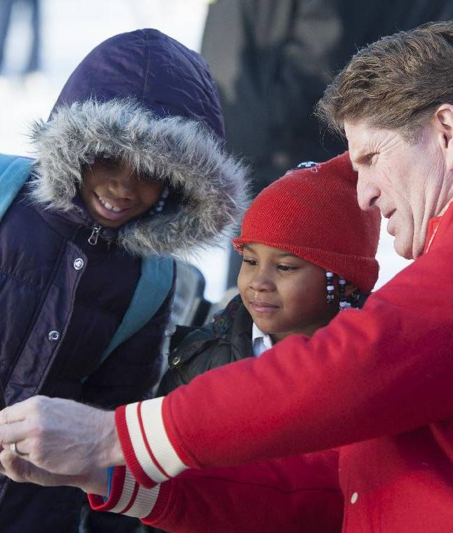 Detroit Red Wings head coach Mike Babcock, right, takes a self portrait using his mobile phone with six-year-old Adriana Weaver, left, and seven-year-old Jayla Marie, center, during an event at Clark Park in Detroit, Monday, Dec. 16, 2013.  The NHL and the Red Wings unveiled a