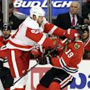 Chicago Blackhawks' Jonathan Toews (19) is checked by Detroit Red Wings' Johan Franzen (93) during the first period of an NHL hockey game in Chicago, Sunday, March 16, 2014. (AP Photo/Nam Y. Huh)