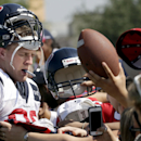 Houston Texans defensive end J.J. Watt, left, signs autographs for fans after an NFL football training camp practice Wednesday, Aug. 13, 2014, in Houston The Associated Press