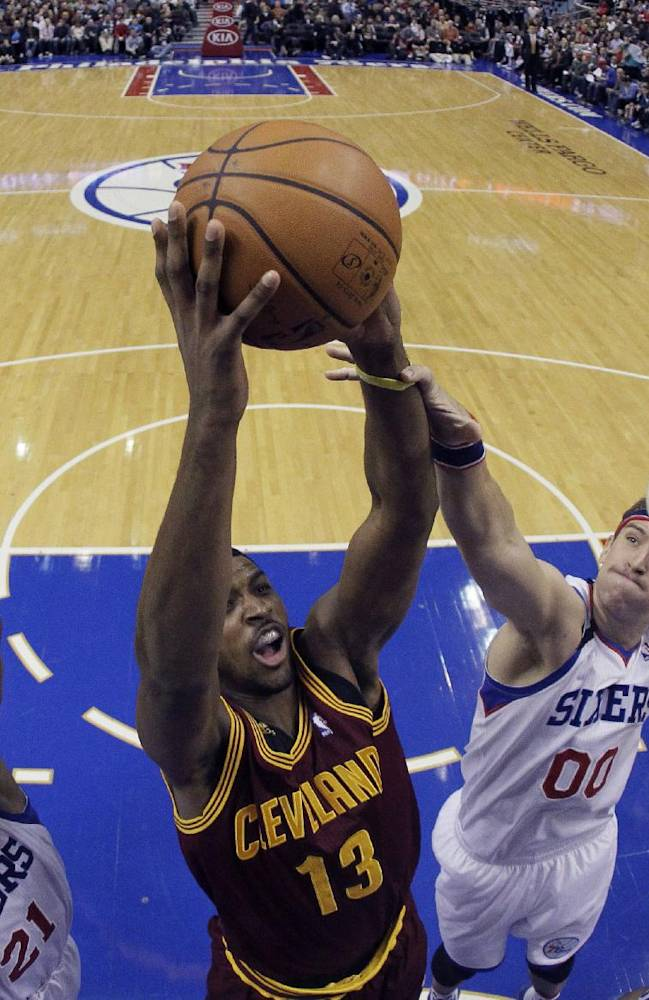 Cleveland Cavaliers' Tristan Thompson (13) goes up for a shot as Philadelphia 76ers' Spencer Hawes (00) and Thaddeus Young (21) defend during the first half of an NBA basketball game, Friday, Nov. 8, 2013, in Philadelphia
