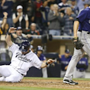 San Diego Padres' Seth Smith slides in with the go ahead run as Colorado Rockies relief pitcher Rex Brothers walks away after two runs scored on a wild pitch and a throwing error in the eighth inning of a baseball game won 5-4 by the Padres Monday, April