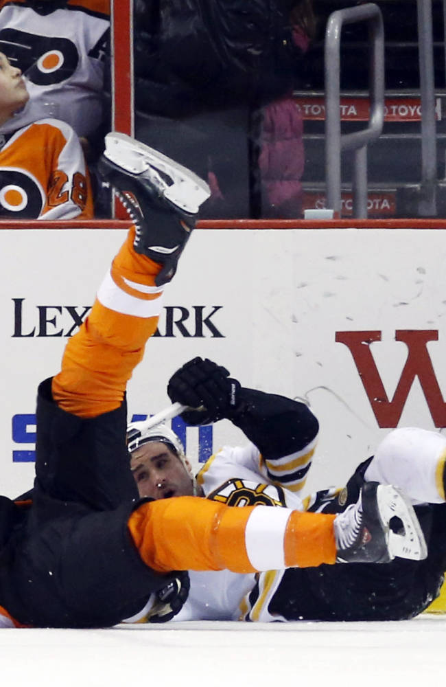 Philadelphia Flyers' Vincent Lecavalier, left, and Boston Bruins' Johnny Boychuk collide during the first period of an NHL hockey game, Sunday, March 30, 2014, in Philadelphia