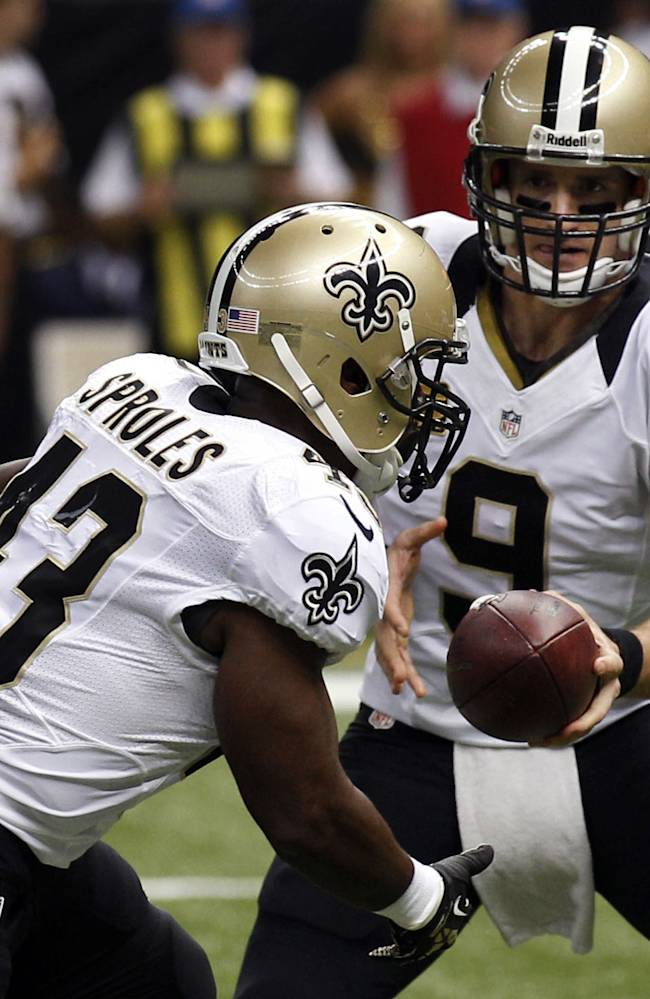New Orleans Saints quarterback Drew Brees (9) hands off to running back Darren Sproles on a touchdown carry in the first half of an NFL football game in New Orleans, Monday, Sept. 30, 2013