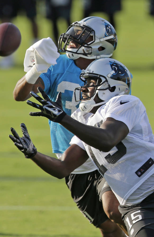 Carolina Panthers' Marvin McNutt, front, reaches for a pass as James Dockery defends during NFL football practice at training camp in Spartanburg, S.C., Saturday, July 26, 2014