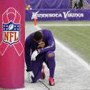 """FILE - In this Oct. 13, 2013, file photo, Minnesota Vikings wide receiver Joe Webb prays at the base of a goal post wrapped to promote breast cancer awareness before an NFL football game against the Carolina Panthers in Minneapolis. The NFL's fourth annual """"Breast Cancer Awareness Month"""" kicks off Thursday night, Oct. 2, 2014,  with the Viking at the Packers  and runs through October.   (AP Photo/Ann Heisenfelt, File)"""