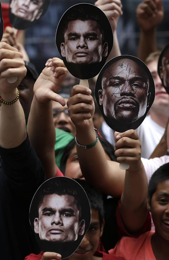 Marcos Maidana fans yell while Floyd Mayweather talks during an outdoor news conference in Times Square, New York, Monday, July 14, 2014. Mayweather will fight Maidana for the second time in Las Vegas, Nevada on Sept. 13, 2014