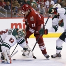 Minnesota Wild's Niklas Backstrom (32), of Finland, makes a save on a shot by Arizona Coyotes' Martin Hanzal (11), of the Czech Republic, as Wild's Christian Folin, right, defends during the second period of an NHL hockey game Saturday, Dec. 13, 2014, in