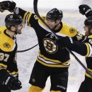 Boston Bruins center Patrice Bergeron, left, is congratulated by teammates David Krejci, center, and Nathan Horton, right, af