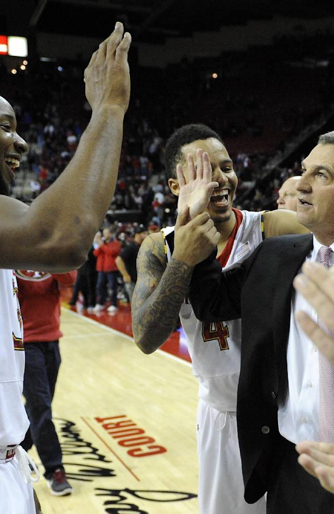 Maryland head coach Mark Turgeon, right, is congratulated by guard Seth Allen (4) and Dez Wells, left, after Maryland defeated Tulsa 85-74 for Turgeon's 300th career win in an NCAA college basketball game, Sunday, Dec. 29, 2013, in College Park, Md