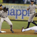 New York Yankees shortstop Derek Jeter left, catches the pick off attempt at second base against a sliding Texas Rangers J.P. Arencibia during the fourth inning of a baseball game Wednesday, July 30, 2014, in Arlington, Texas. Arencibia advanced from first on a wild pitch. (AP Photo/LM Otero)