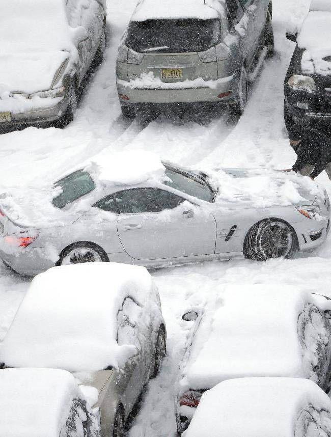 Snow-covered cars occupy a parking lot at Lincoln Financial Field during the second half of an NFL football game between the Philadelphia Eagles and the Detroit Lions, Sunday, Dec. 8, 2013, in Philadelphia