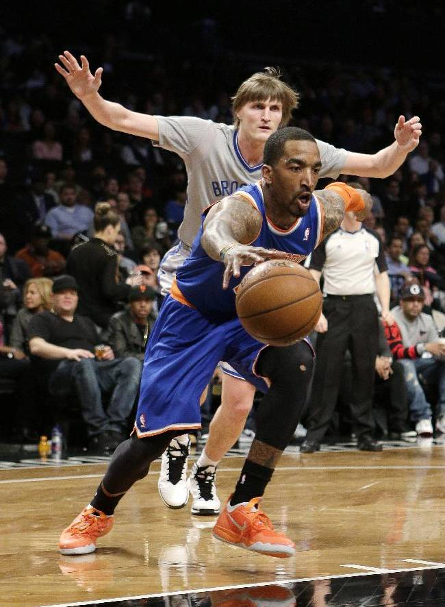 New York Knicks' J.R. Smith (8) drives past Brooklyn Nets' Andrei Kirilenko, of Russia, during the second half of an NBA basketball game Tuesday, April 15, 2014, in New York. The Knicsk won 109-98