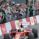Brazilian Formula One racing driver Felipe Massa greets the audience as he drives a Ferrari car during a promotional event in Warsaw, Poland, Saturday, May 18, 2013. (AP Photo/Alik Keplicz)