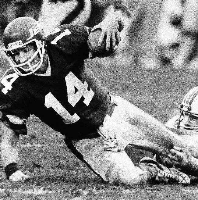 FILE- In this Jan. 23, 1983 file photo, New York Jets quarterback Richard Todd (14) goes down at the hands of Miami Dolphin Kim Bokamper, defensive end, during second half of the AFC Championship game in Miami. Todd led the Jets to the playoffs only twice in his eight seasons