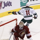 Minnesota Wild's Zach Parise (11) skates away after scoring a goal against Arizona Coyotes' Devan Dubnyk, left, during the shootout of an NHL hockey game Saturday, Dec. 13, 2014, in Glendale, Ariz. The Wild defeated the Coyotes 4-3 in a shootout The Asso