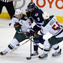 Minnesota Wild's Ryan Suter (20) and Erik Haula (56) sandwich Winnipeg Jets' Evander Kane (9) during third period NHL hockey action in Winnipeg, Manitoba, on Monday, April 7, 2014 The Associated Press