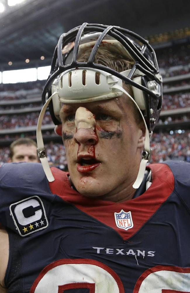 In this Sunday, Sept. 29, 2013 file photo, a bloodied Houston Texans' J.J. Watt walks off the field after the team's overtime loss to the Seattle Seahawks in an NFL football game in Houston. Watt's penchant for violent collisions resulted in a deep gash on the bridge of his nose during the game, which required six stitches. The gash kept opening in subsequent games, so now that the season is winding down, Watt tells The Associated Press he'll look into having plastic surgery in the offseason to repair the injury