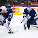 Toronto Maple goalie James Reimer, right, makes a save as Montreal Canadiens forward David Desharnais, left, as Maple Leafs defenceman Morgan Rielly, center, defends during the first period of an NHL hockey game in Toronto on Saturday, March 22, 2014 The