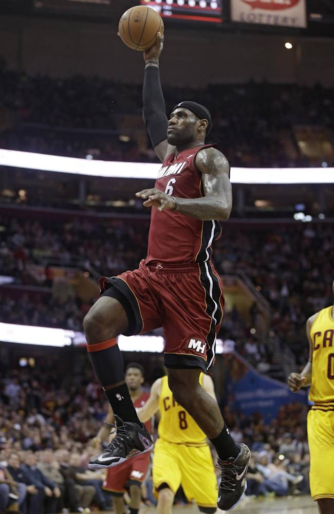 Miami Heat's LeBron James (6) jumps to the basket against the Cleveland Cavaliers during the first quarter of an NBA basketball game Tuesday, March 18, 2014, in Cleveland