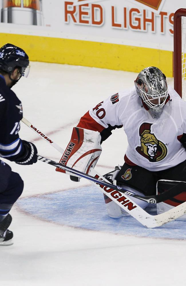 Winnipeg Jets' Matt Halishchuk (15) scores on a breakaway against Ottawa Senators' goaltender Robin Lehner (40) during second period pre-season NHL action in Winnipeg on Sunday, Sept. 15, 2013