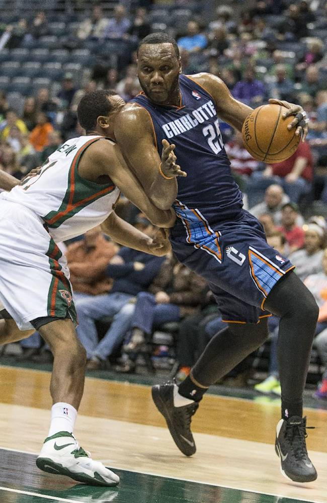 Milwaukee Bucks' John Henson, left, tries to stop Charlotte Bobcats' Al Jefferson during the first half of an NBA basketball game on Sunday, March 16, 2014, in Milwaukee