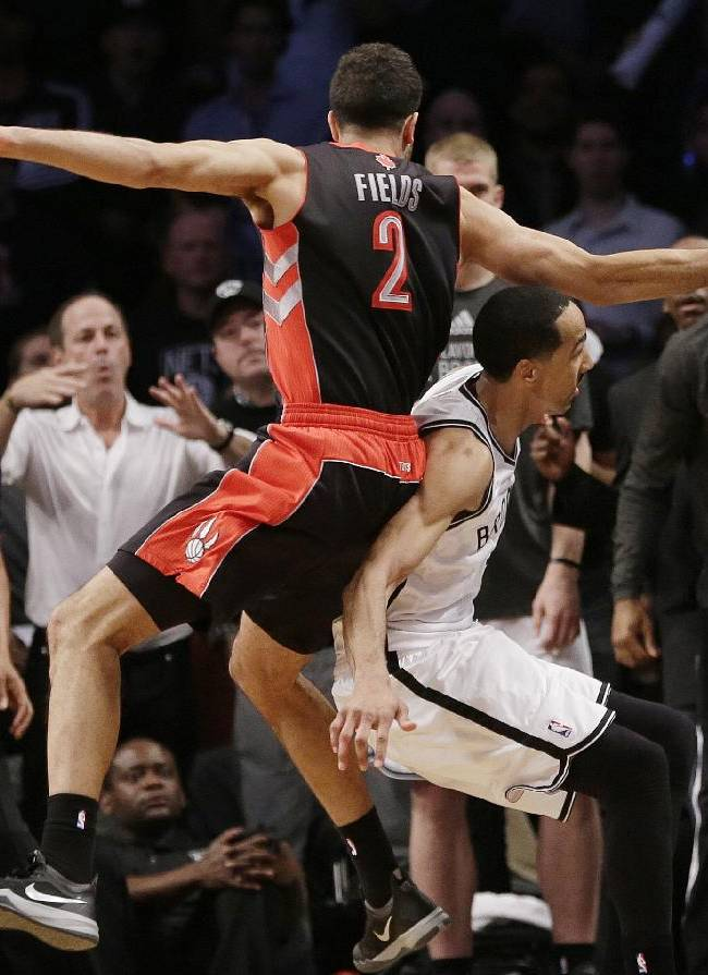 Toronto Raptors' Landry Fields, above, falls over Brooklyn Nets' Shaun Livingston, below as he chased a ball out of bounds during the second half of Game 3 of an NBA basketball first-round playoff series Friday, April 25, 2014, in New York. The Nets won 102-98