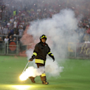 Firefighter carries a flare off the pitch during the Group E Champions League soccer match between Roma and Bayern Munich at the Olympic stadium, in Rome, Tuesday, Oct. 21, 2014 The Associated Press