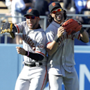 San Francisco Giants left fielder Gregor Blanco, left, leaps with center fielder Angel Pagan, right, after defeating the Los Angeles Dodgers 7-2 in a baseball game on Saturday, April 5, 2014, in Los Angeles The Associated Press