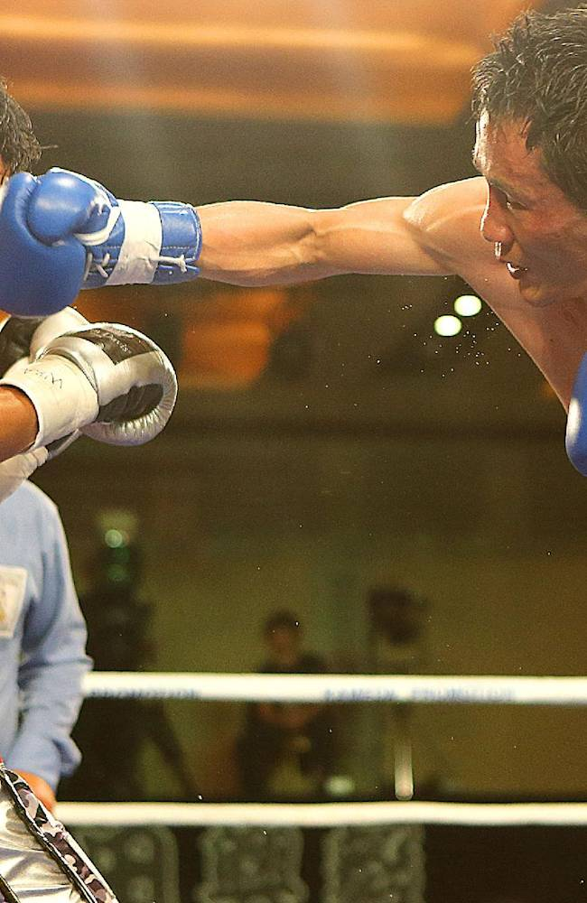 Challenger Son Jeong-ho, right, of South Korea lands a punch to champion Koki Kameda of Japan during the WBA bantamweight title bout in Jeju, Korea Tuesday, Nov. 19, 2013. Kameda defeated Son with a split decision