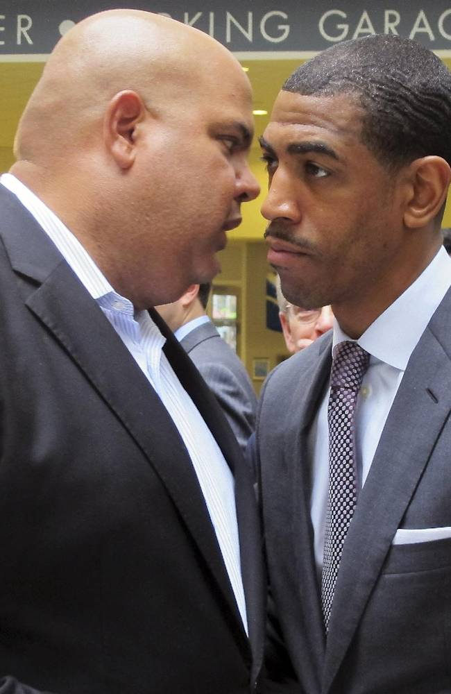 University of Connecticut Athletic Director Warde Manuel, left, and head basketball coach Kevin Ollie speak after a news conference in Hartford, Conn., Friday, May 16, 2014, to discuss the choice of the XL Center as the site of the 2015 American Athletic Conference basketball tournament. Manuel and Ollie both said they are continuing to negotiate a new contract for the coach and have no deadline. Ollie's current deal, worth just under $7 million, runs through the end of the 2017-18 season. He made just over $1.6 million, with bonuses for the NCAA tournament run, last season