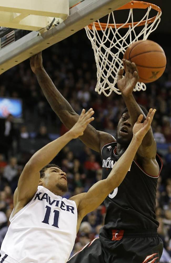 Xavier guard Dee Davis (11) drives against Cincinnati forward Justin Jackson in the first half of an NCAA college basketball game, Saturday, Dec. 14, 2013, in Cincinnati