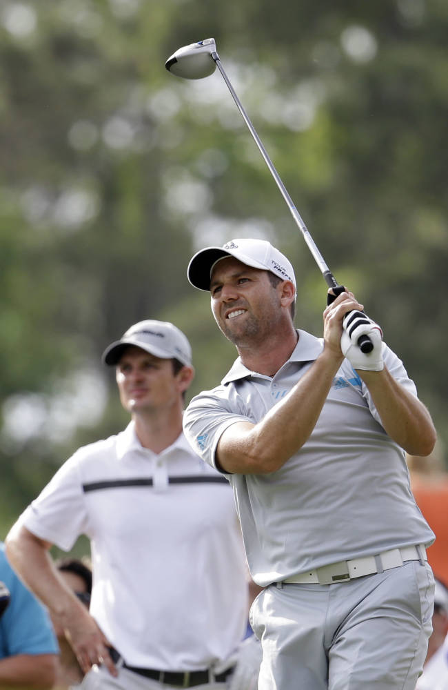 Sergio Garcia of Spain, looks at his shot from the 16th tee as Justin Rose of England waits his turn, during the third round of The Players championship golf tournament at TPC Sawgrass, Saturday, May 10, 2014 in Ponte Vedra Beach, Fla