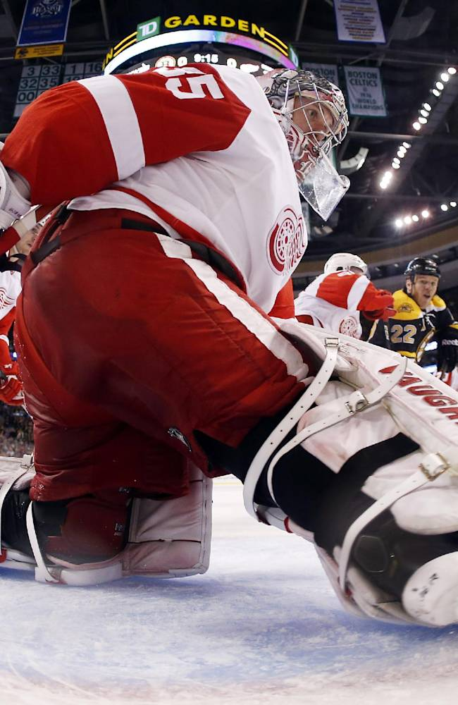 In this photo taken with a fisheye lens, Detroit Red Wings goalie Jimmy Howard looks behind the net for the puck during the second period of Detroit's 1-0 win over the Boston Bruins in Game 1 of a first-round NHL hockey playoff series, in Boston on  Friday, April 18, 2014