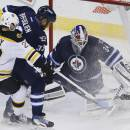 Winnipeg Jets goaltender Michael Hutchinson (34) stops a shot from Boston Bruins' Chris Kelly (23) as Jets' Dustin Byfuglien (33) defends during the first period of an NHL hockey game Friday, Dec. 19, 2014, in Winnipeg, Manitoba. (AP Photo/The Canadian Press, John Woods)