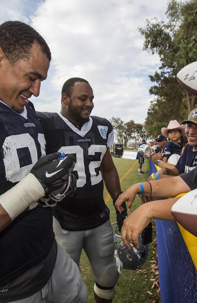 Dallas Cowboys defensive end Tyrone Crawford (98), left, and teammate defensive end Jeremy Mincey (92) sign autographs at the end of practice at NFL football training camp, Wednesday, July 30, 2014, in Oxnard, Calif