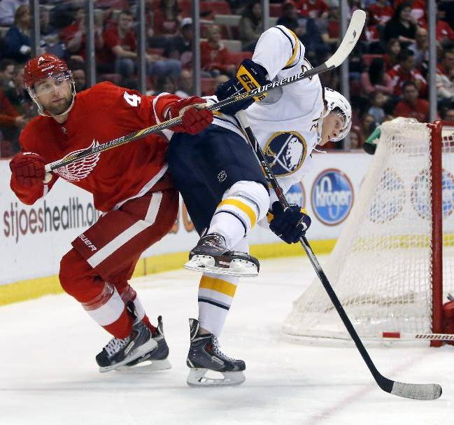 Detroit Red Wings' Jakub Kindl (4), of the Czech Republic, knocks Buffalo Sabres' Luke Adam (72) off-balance during the first period of an NHL hockey game Friday, April 4, 2014, in Detroit