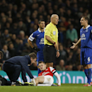 Referee Howard Webb, in yellow, talks to Everton's Phil Jagielka who has his arms out as Arsenal's Jack Wilshere receives treatment during the English Premier League soccer match between Arsenal and Everton at the Emirates Stadium in London, Sunday, Dec.