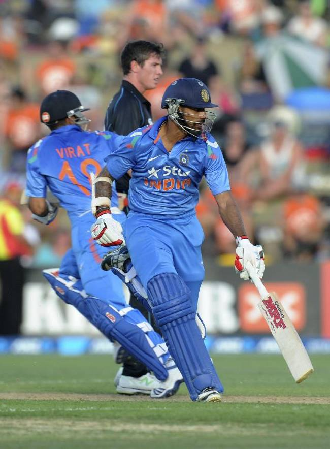 India's Virat Kohli, left and Shikhar Dhawan cross against New Zealand in their first one day international cricket match at McLean Park in Napier, New Zealand, Sunday, Jan. 19, 2014