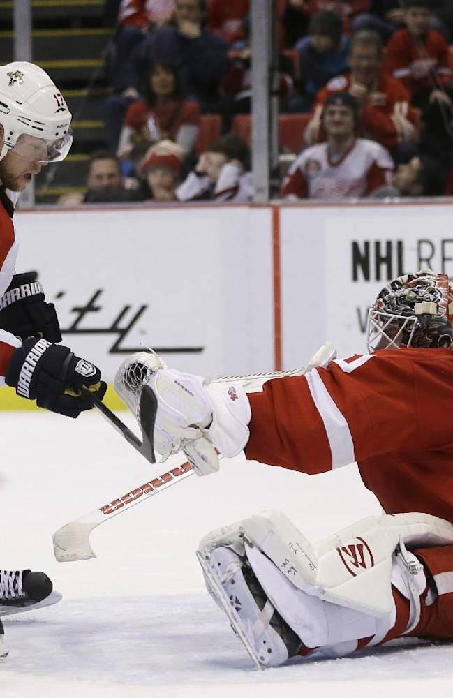 Detroit Red Wings goalie Jonas Gustavsson, right, of Sweden, catches a shot hit by Florida Panthers center Jesse Winchester (17) during the second period of an NHL hockey game in Detroit, Sunday, Jan. 26, 2014