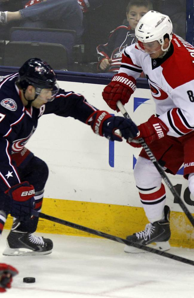 Carolina Hurricanes' Andrei Loktionov, right, of Russia, passes the puck against Columbus Blue Jackets' Jack Johnson in the third period of an NHL hockey game in Columbus, Ohio, Tuesday, March 18, 2014. Carolina won 3-1