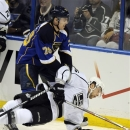 St. Louis Blues' Adam Cracknell (79) and  Los Angeles Kings' Jake Muzzin, right, compete for the puck during the second perio